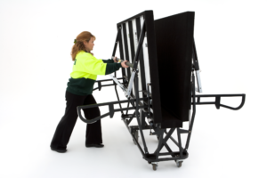 Stand in the centre of the folded stage. Using the crossbar, gently pull the upper chrome leg outward and upward. Lower the stage wing until the D-Legs are on the floor. Repeat on the opposite side.