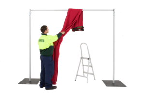 Carefully throw the drape over the crossbar to avoid lifting the drape.
